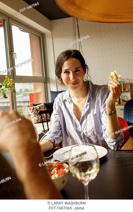 Smiling woman holding bread while looking at man in house