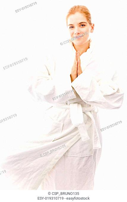 Young woman standing in bathrobe and practicing yoga