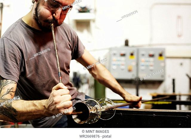 A glassblower working on a shaped piece of glass and using a chisel to shape and finish the object