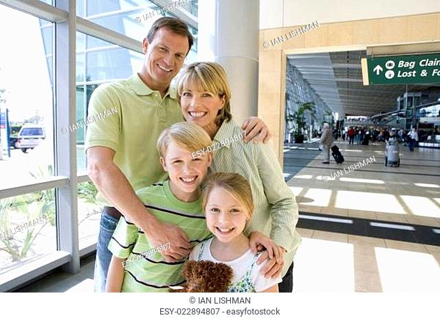 Family standing in airport, smiling, front view, portrait