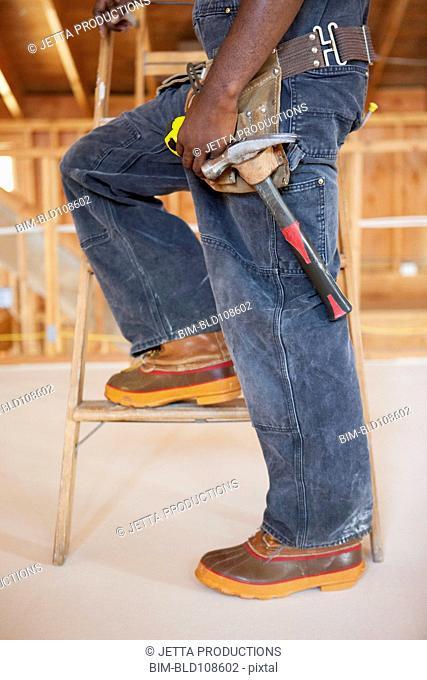 Black construction worker standing on ladder
