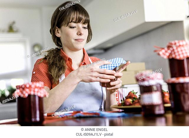 Woman packing homemade strawberry jam