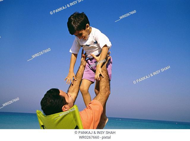 A father hoisting his son near the vast sea