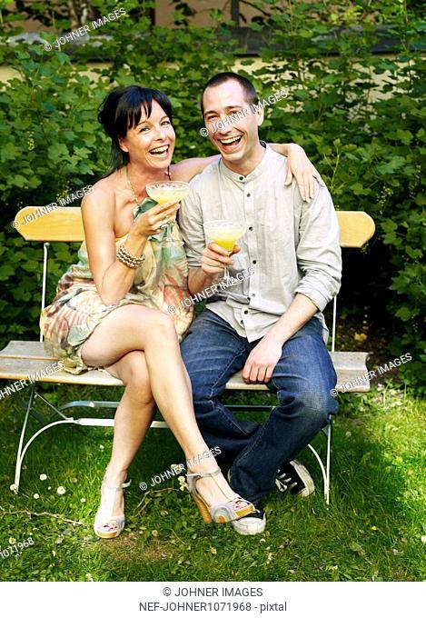 Couple drinking orange juice in backyard