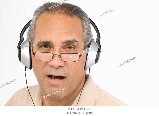 Portrait of a mature man wearing headphones and singing