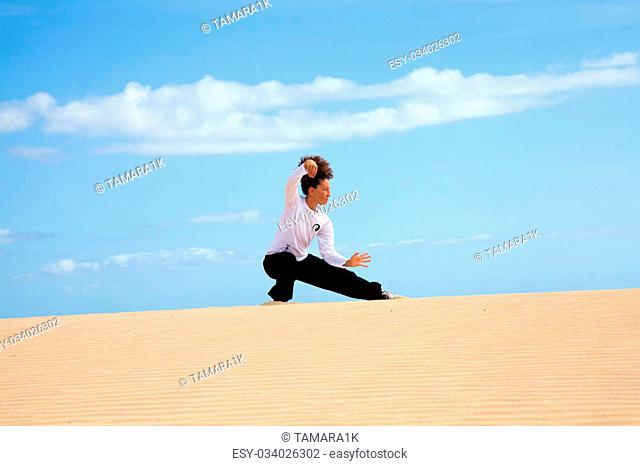 Tai chi in the dunes - young woman in black and white making tai chi moves