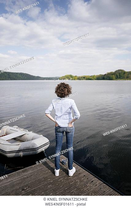 Woman standing on jetty with moored boat