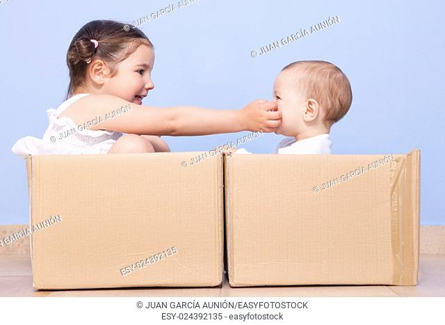 Baby brother and toddler sister playing in cardboard boxes
