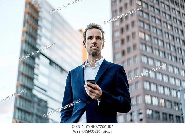 Germany, Berlin, portrait of businessman with smartphone