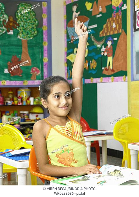 South Asian Indian girl raising hand for replaying answer in nursery school MR
