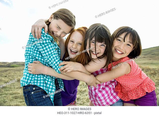 Portrait of playful schoolgirls embracing at field