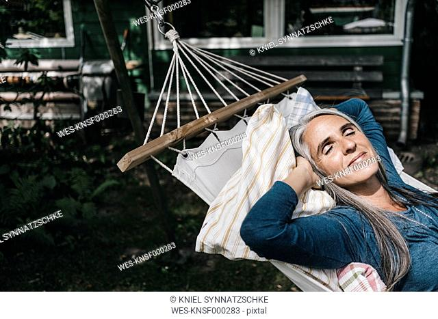 Woman relaxing in hammock in the garden