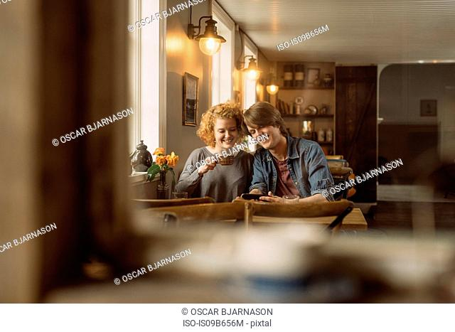 View through cafe window of couple on date smiling