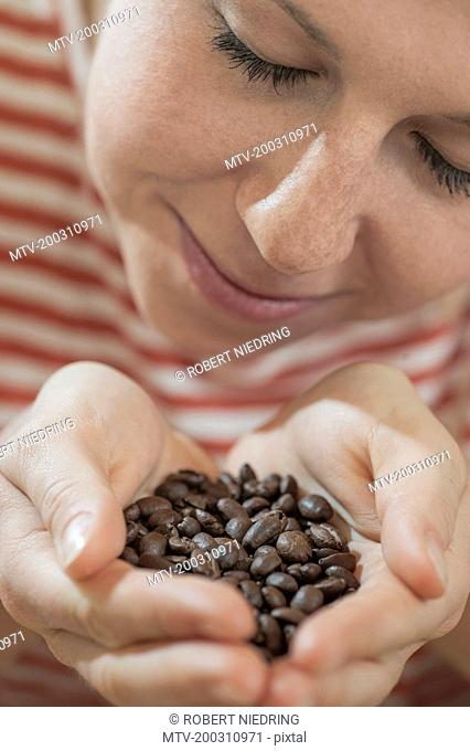 Young woman taking a smell of roasted coffee beans