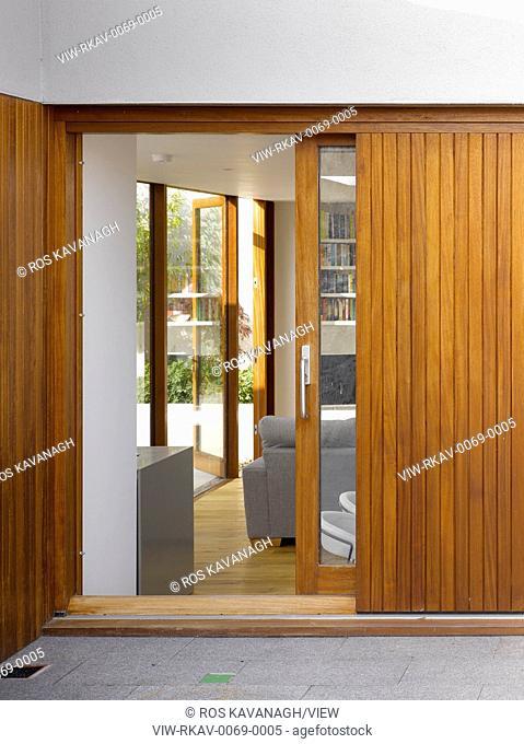 Exterior view through sliding door showing living area through to courtyard. Cottage Malahide, Malahide, Ireland. Architect: Amanda Bone Architects, 2014