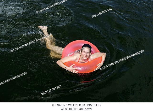 Germany, Wustrow, girl swimming with floating tire in Labussee