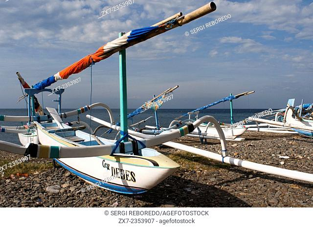 A fisherman with several fishing boats on the beach of Amed, a small fishing village in East Bali. Amed is a long coastal strip of fishing villages in East Bali