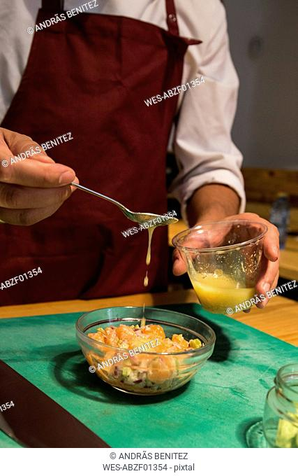 Man pouring vinaigrette with a spoon in a bowl with peruvian ceviche