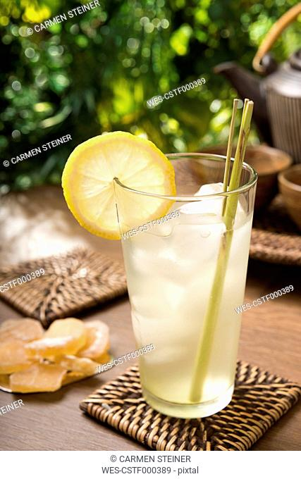 Ginger lemon tea in a glass with fresh lemongrass, candied ginger