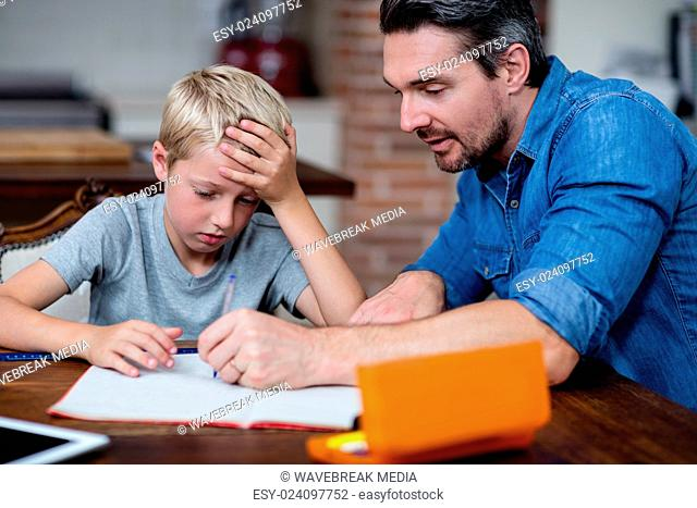Father helping son with his homework in kitchen
