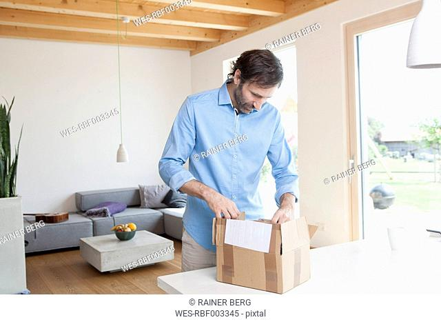Mature man at home unpacking parcel
