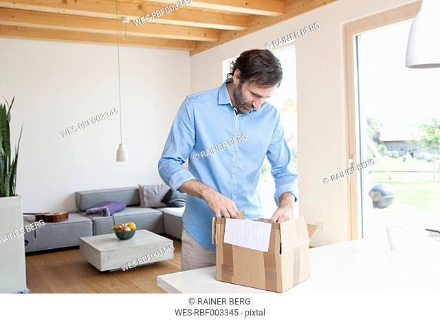 Mature man at home unpacking parcel