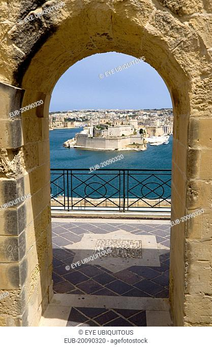 Fort Saint Angelo on Vittoriosa one of the Three Cities in Valletta Harbour seen through an arch in the Upper Barrakka Gardens in Valletta
