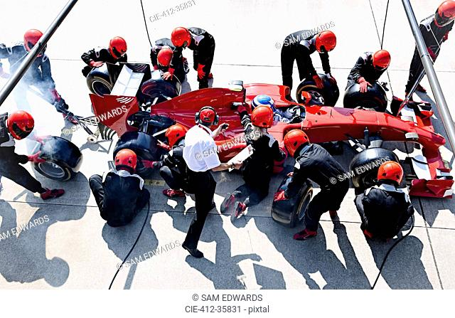 Manager with stopwatch timing pit crew replacing tires on formula one race car in pit lane