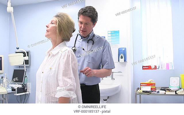 TD Male doctor examining female patient with back pain