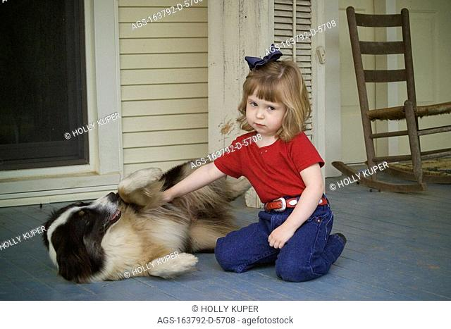 Agriculture - A little ranch girl plays with her Australian Shepherd dog on the front porch of her familyÕs home / TX - Tennessee Colony
