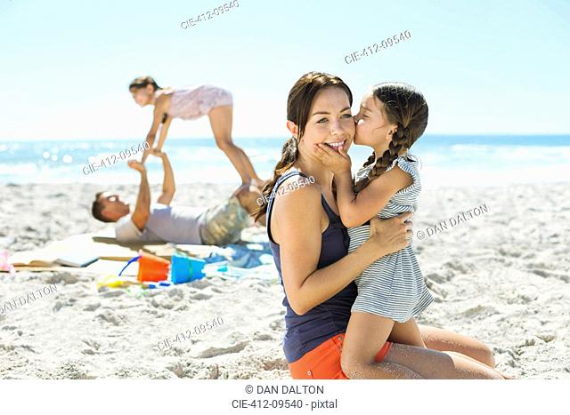 Girl kissing mother's cheek at beach