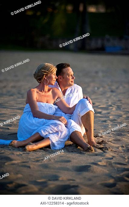 A couple sitting on the beach at the Empire Hotel and Country Club; Bandar Seri Begawan, Brunei