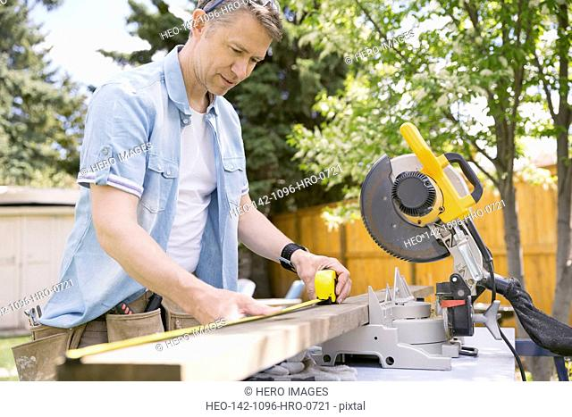Man measuring wood plank at table saw