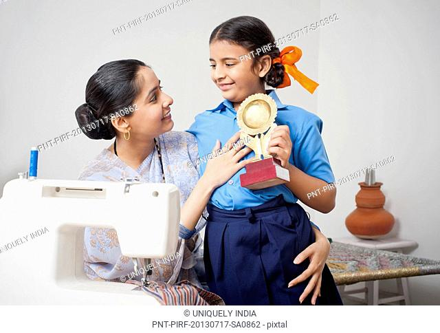 Girl showing a winning trophy to her mother