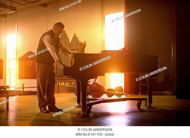 Caucasian man playing piano on stage