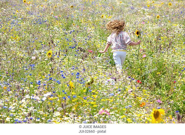 Girl holding sunflower running through field of wildflowers