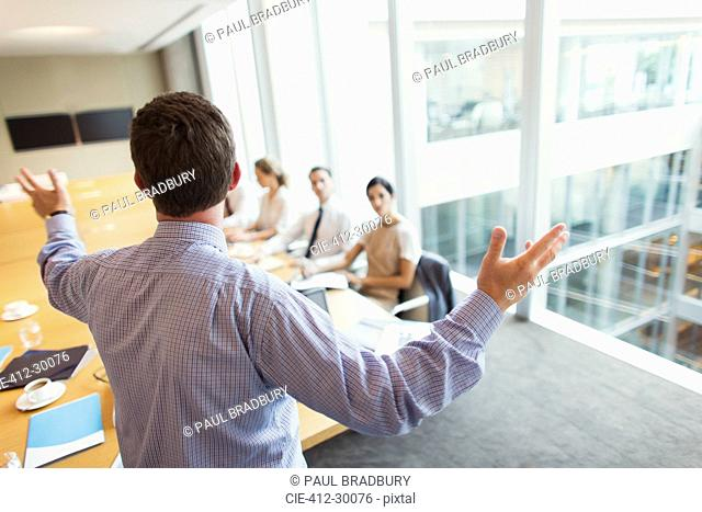 Businessman gesturing to colleagues in conference room meeting