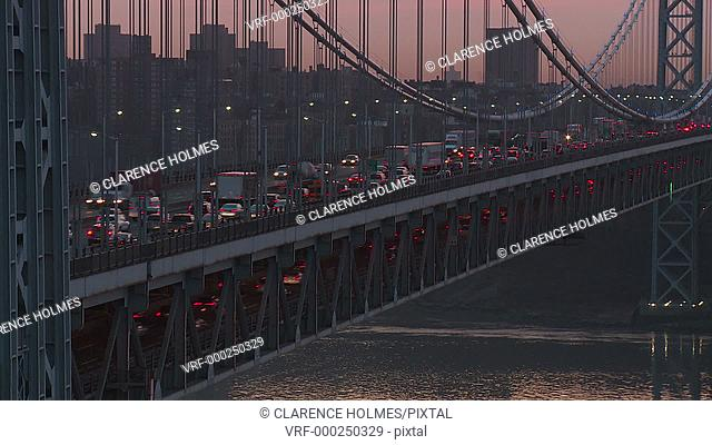 Morning rush hour traffic on the George Washington Bridge crosses the Hudson River between New Jersey and New York just before sunrise