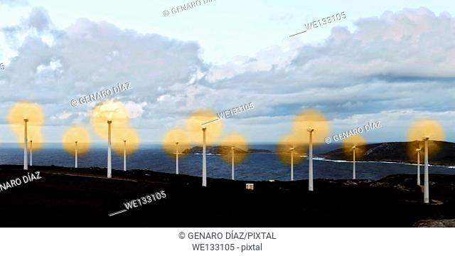 wind turbines farm at sunset with sea in background in Galicia, Spain