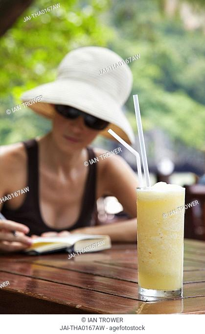 Woman at beachside restaurant with pineapple drink, Railay, Krabi Province, Thailand MR