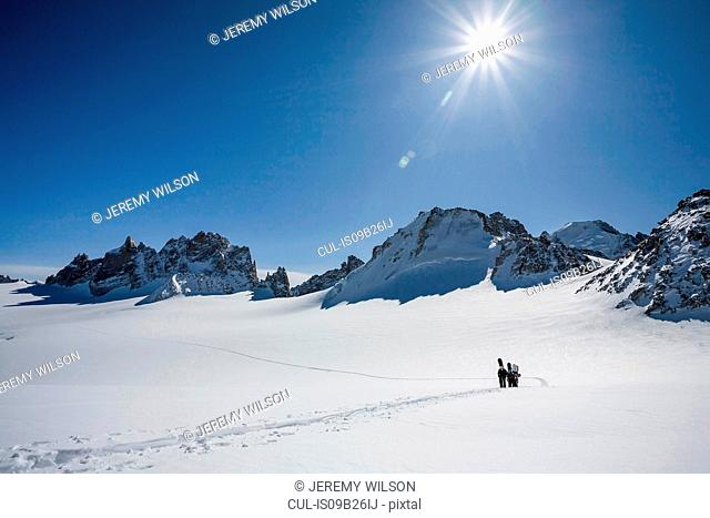 Four male snowboarders hiking across snow-covered landscape, Trient, Swiss Alps, Switzerland