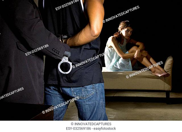 Cop arresting a man for domestic violence and female victim in the background