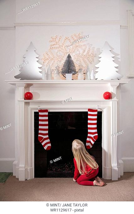 A young girl looking expectantly up the chimney awaiting the arrival of Father Christmas