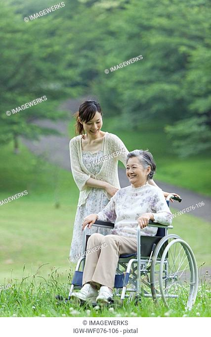 Japan, Tokyo Prefecture, Senior woman in wheelchair with daughter, smiling
