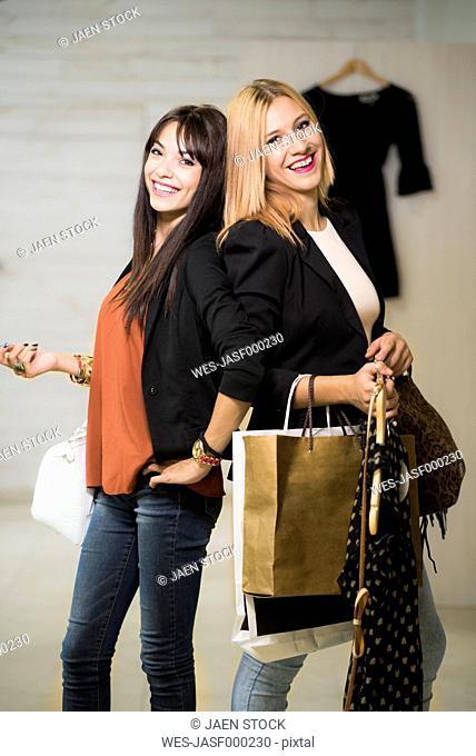 Young women in fashion boutique carrying shopping bags