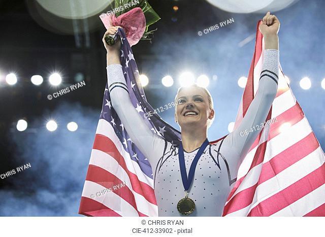 Enthusiastic female gymnast celebrating victory holding American flag on winners podium