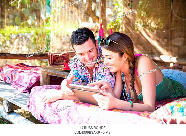 Couple using digital tablet smiling