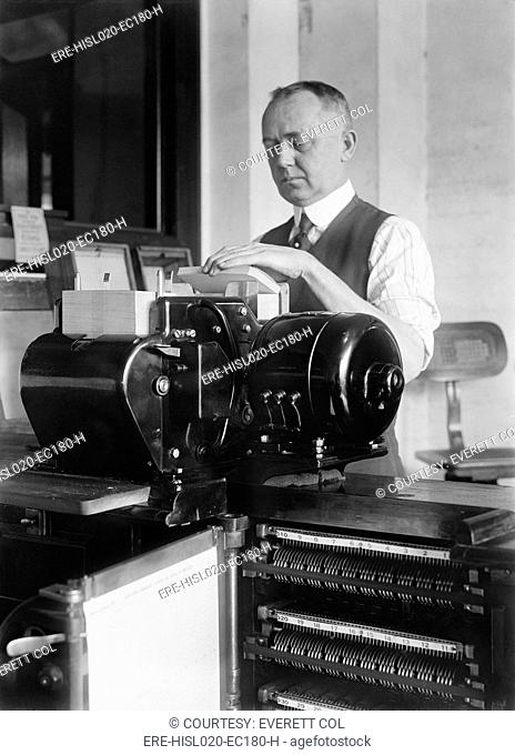 Man loading punch cards into a tabulating machine used in the 1920 United States census. It was a predecessor of electronic computers