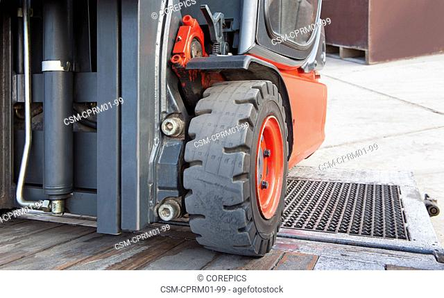 Close up of a forklift on the ramp of a trailer