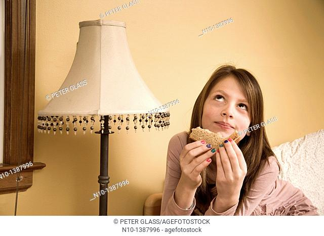 Preteen girl eating a sandwich in her bedroom
